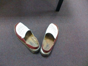 Empty well-worn red and white shoes against institutional carpet
