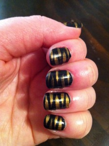 black nails with gold stripes in vague zebra pattern