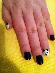 black nails with little panda faces on the accent nails